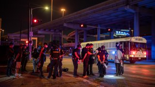 A group of people being placed under arrest stand by a Harris County Jail bus after protesters were apprehended in a fenced in area on June 2, 2020 in Houston, Texas.