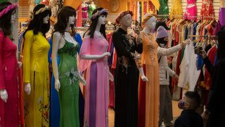 """Westminster, CA - February 10: Shoppers view mannequins dressed in the áo dài, the traditional Vietnamese dress outfit, at the Asian Garden Mall in preparation for the Lunar New Year in Little Saigon, Westminster Wednesday, Feb. 10, 2021. For those who celebrate Lunar New Year, which starts Friday, Feb. 12, COVID has forced them to avoid touching cash and stuff traditional red envelopes normally filled with """"lucky"""" money instead with checks, Lotto tickets, gift cards and the like. It will be the Year of the Ox. People flocked to Little Saigon to purchase holiday wares, traditional Vietnamese outfits, baked goods or flowers set up at store entrances or along the sidewalk."""