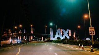 LAX gateway pylons illuminate amber.