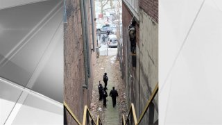 Police respond to the scene of an alleged thief clinging to the side of a building