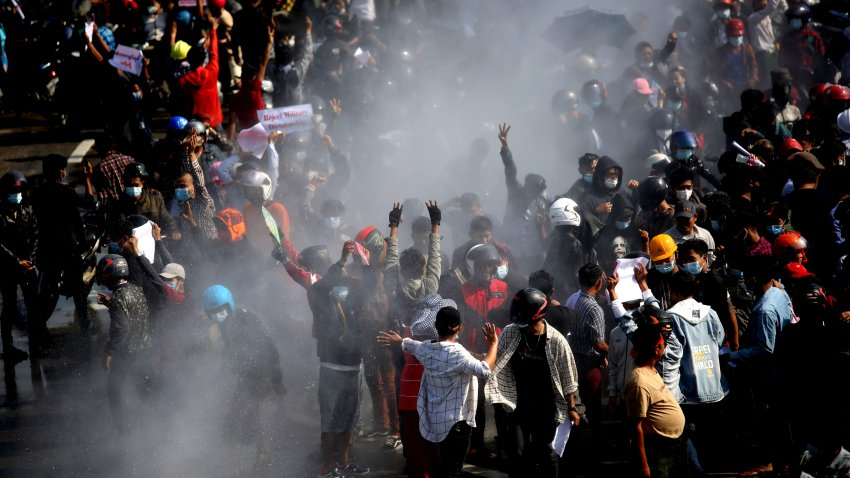 In this Feb. 8, 2021, file photo, protesters are sprayed with water fired from a police truck's water cannon in Naypyitaw, Myanmar.