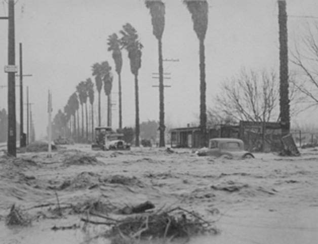 Debris and a few cars can be seen floating on Sherman Way in the San Fernando Valley. This 1938 image was taken from Mason Avenue looking east. The palm fronds indicate a southerly wind.