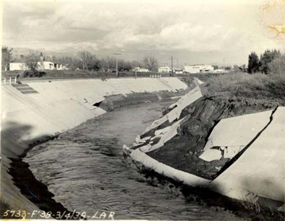 This 1938 image shows the LA River just before it receives the Tujunga Wash. By 1938, some portions of the river had been channelized (lined in concrete). The flood waters managed to rip away concrete siding from this portion of the river.
