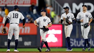 New York Yankees, from left, Didi Gregorius, Brett Gardner, Cameron Maybin, and Giancarlo Stanton celebrate after defeating the Houston Astros
