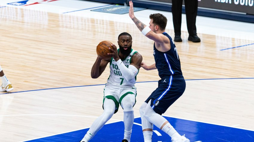 Boston Celtics guard Jaylen Brown (7) makes a move toward the basket as Dallas Mavericks guard Luka Doncic (77) defends during the first half of an NBA basketball game in Dallas, Tuesday, Feb. 23, 2021.