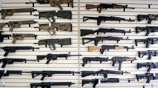 FILE - In this Oct. 2, 2018, file photo, semi-automatic rifles fill a wall at a gun shop in Lynnwood, Wash. With Democrats controlling the presidency and Congress, Republican state lawmakers concerned about the possibility of new federal gun control laws aren't waiting to react. Legislation in at least a dozen states seeks to nullify any new restrictions, such as ammunition limits or a ban on certain types of weapons.