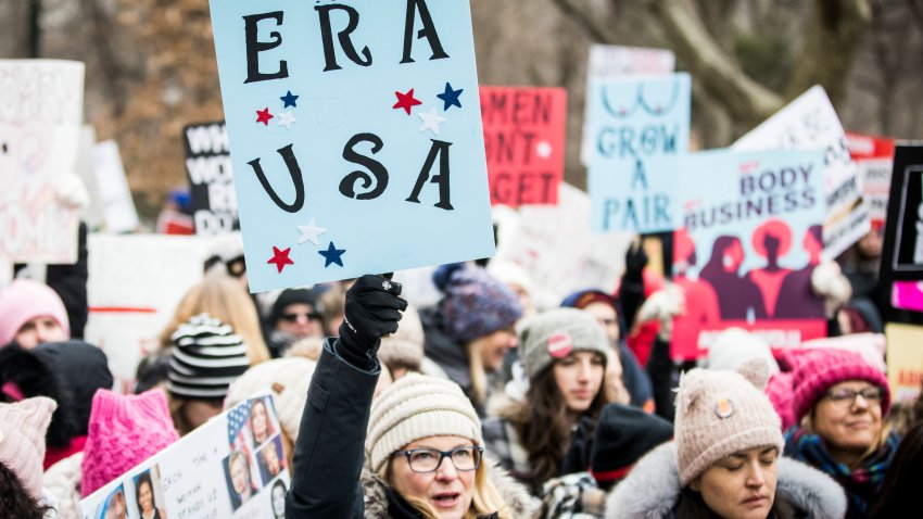 """MANHATTAN, NY - JANUARY 18: A marcher holds a sign that say, """"ERA USA"""" during the Woman's March in the borough of Manhattan in NY on January 18, 2020, USA. On April 15, 2020 Hulu is launching a series entitled """"Mrs. America"""" which tells the story of the movement to ratify the Equal Rights Amendment (ERA), and the unexpected backlash led by a conservative woman named Phyllis Schlafly, Through the eyes of the women of the era -- both Schlafly and second-wave feminists Gloria Steinem, Betty Friedan, Shirley Chisholm, Bella Abzug and Jill Ruckelshaus -- the series explores how one of the toughest battlegrounds in the culture wars of the '70s helped give rise to the Moral Majority and forever shifted the political landscape."""