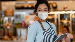 FILE - A waitress working at a restaurant wearing a face mask to avoid the spread of coronavirus.