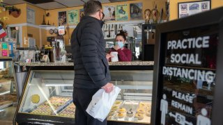 A person wearing a protective mask picks up an order at a cafe.