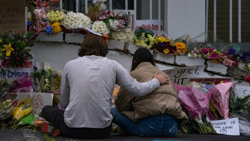 People bring flowers to the memorial sight set up outside of The Gold Spa on March 19, 2021 in Atlanta, Georgia.