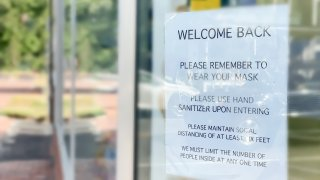 business reopening sign posted amid covid-19 pandemic in storefront window