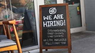 "In this March 5, 2021, file photo, a ""we are hiring sign"" in front of the Buya restaurant in Miami, Florida. The restaurant is looking to hire more workers as the U.S. unemployment rate drops to 6.2 percent, as many restaurants and bars reopen. Officials credit the job growth to declining new COVID-19 cases and broadening vaccine immunization that has helped more businesses reopen with greater capacity."
