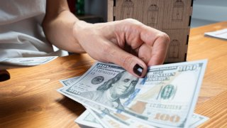 A hand holds $100 bills as a miniature house sits behind it.