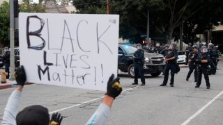 A person holds a Black Lives Matter sign during protests in Los Angeles.