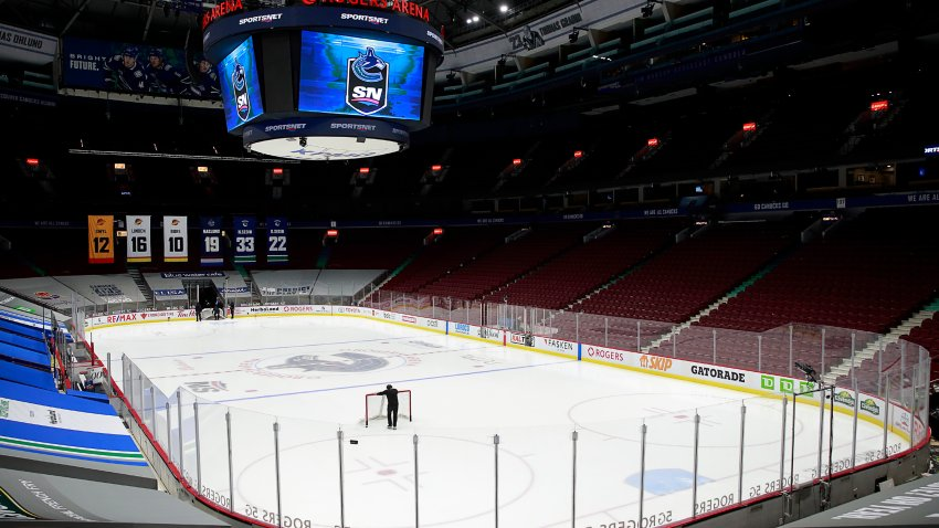 VANCOUVER, BC - MARCH 31: A rink attendant pushes a game net off the ice after the NHL game between the Calgary Flames and the Vancouver Canucks was postponed due to a positive COVID test result of a player at Rogers Arena on March 31, 2021 in Vancouver, British Columbia, Canada.