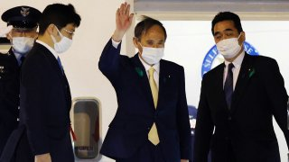 Japan's Prime Minister Yoshihide Suga (2nd-R) waves as he departs for the US from Tokyo's Haneda airport on April 15, 2021 to become the first foreign leader to hold talks with US president.