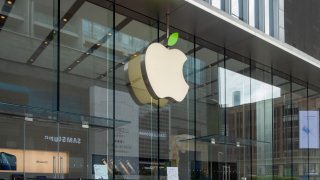 """In this April 22, 2021, file photo, the Apple logo lights up its """"green leaves"""" outside the Apple Store on Nanjing Road in response to the 52nd Earth Day in Shanghai."""