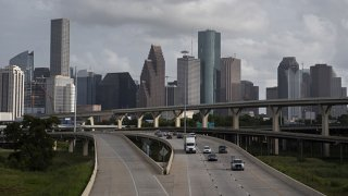 FILE: Traffic moves past the skyline of Houston, Texas, U.S., on Saturday, June 27, 2020.