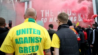"""A fan wears a shirt with a """"United Against Greed"""" message, as fans gather to protest against the Glazer family, the owners of Manchester United, outside Old Trafford stadium"""