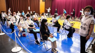 Participants take part in a Covid-19 coronavirus vaccination simulation by Japan's Self-Defence Forces at an inoculation centre in Tokyo on May 21, 2021.