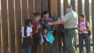 United States Border Patrol agents detain families from Central and South America who have been crossing into the United States from Mexico to ask for asylum, April 30, 2021 outside of Yuma, Arizona.