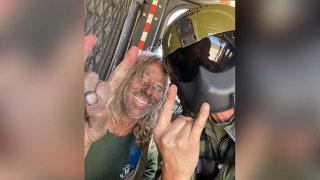 A hiker found after spending five days lost in Angeles National Forest poses for a photo with a search team member.