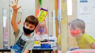 kindergarten students wear masks and are separated by plexiglass during a math lesson