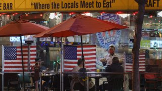 Patrons sits outdoors for dinner separated by plastic dividers with national flags at Mel's drive-in restaurant on Sunset Boulevard on Tuesday, Nov. 24, 2020, West Hollywood, Calif.