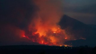 In this photo provided by Joseph Pacheco, a wildfire is seen burning in Globe, Ariz., on Monday, June 7, 2021. Firefighters in Arizona were fighting Tuesday to gain a foothold into a massive wildfire, one of two that has forced thousands of evacuations in rural towns and closed almost every major highway out of the area.