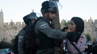 """An Israeli border police officer faces off with a Palestinian woman at a protest at the Damascus Gate to the Old City of Jerusalem Thursday, June 17, 2021 against incendiary chants used by ultranationalist Israelis at their """"Flags March"""" at the same site on Tuesday."""