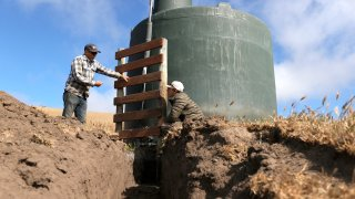 Ranchers Jim Jensen (R) and Bill Jensen (L) stand by a water tank as they work on a water project to try and get more water to their ranch from a well.