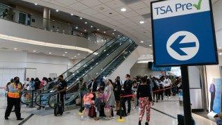 Passengers wearing protective masks wait in lines to pass through a TSA checkpoint at Hartsfield-Jackson Atlanta International Airport in Atlanta, Georgia.