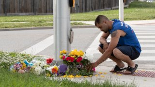 A man brings flowers and pays his respects at the scene where a man driving a pickup truck struck and killed four members of a Muslim family in London, Ontario, Canada on June 7, 2021.