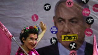 An Israeli protester waves towards a poster depicting Prime Minister Benjamin Netanyahu during a demonstration against him in front of his residence in Jerusalem, on June 12, 2021, a day ahead of a vote on a new government at the Knesset which would end his rule.