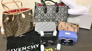 Counterfeit goods laid out on a table, including a fake Louis Vuitton bag, Givenchy shirt, Cialis pills, Chanel sunglasses and more. The goods were seized by U.S. Customs and Border Protection.
