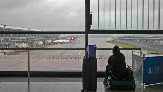 A passenger sits on her luggage watching passenger airplanes parked on the tarmac after all flights were canceled at Pudong International Airport in Shanghai, China