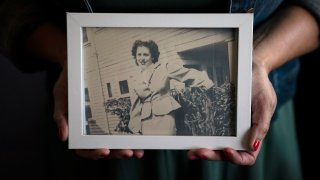 Stacy Cordova, whose aunt was a victim of California's forced sterilization program that began in 1909, holds a framed photo of her aunt Mary Franco, Monday, July 5, 2021, in Azusa, Calif. Franco was sterilized when she was 13 in 1934. Franco has since died, but Cordova has been advocating for reparations on her behalf.