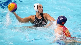 Maggie Steffens holds a water polo ball up in the pool.