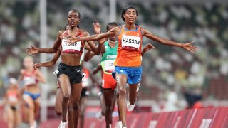 Sifan Hassan of Team Netherlands crosses the finish line first ahead of Agnes Jebet Tirop of Team Kenya in Heat 1 of the Women's 5000m Round 1