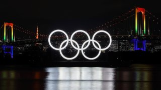 The Olympic rings lit up at night in front of Tokyo's Rainbow Bridge