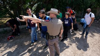 In this Wednesday, June 16, 2021, file photo, A Texas Department of Public Safety officer in Del Rio, Texas directs a group of migrants who crossed the border and turned themselves in.