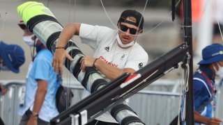Erik Heil of Team Germany packs up his boat after sailing competition is postponed
