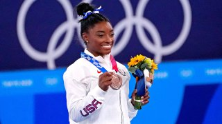 Simone Biles poses with bronze medal
