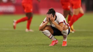Carli Lloyd, head in hands, after USA lost to Canada in women's soccer at the Olympics