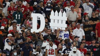A Tampa Bay Buccaneers fan holds a sign during the first half of an NFL football game against the Dallas Cowboys