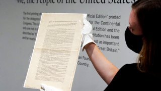 Ella Hall, a specialist in Books and Manuscripts at Sotheby's, in New York, holds a 1787 printed copy of the U.S. Constitution