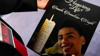 Mourner holding a Daunte Wright program