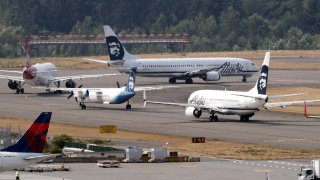 Planes line-up to take a turn onto the center runway for take-off at Seattle-Tacoma International Airport Monday, Aug. 13, 2018, in SeaTac, Wash. The plane at center left, an Alaska Airlines Q400 turboprop airplane, is the same model of aircraft stolen from the airport by an airline ground agent on Friday, which later crashed into crashed into a small island in the Puget Sound, killing the man.