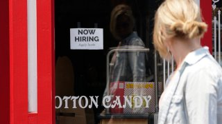 """A """"NOW HIRING"""" sign is posted in the window of The Wharf Chocolate Factory at Fisherman's Wharf in Monterey, Calif., Friday, Aug. 6, 2021. California employers are adding new jobs at a record-breaking pace even as the state's unemployment claims remain stubbornly high, a sign the delta variant could be giving people pause about returning to work."""