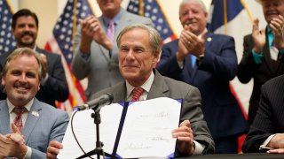 Texas Gov Greg Abbott holds up Senate Bill 1, also known as the election integrity bill, after he signed it into law in Tyler, Texas, Sept. 7, 2021. The sweeping bill signed Tuesday by the two-term Republican governor further tightens Texas' strict voting laws.